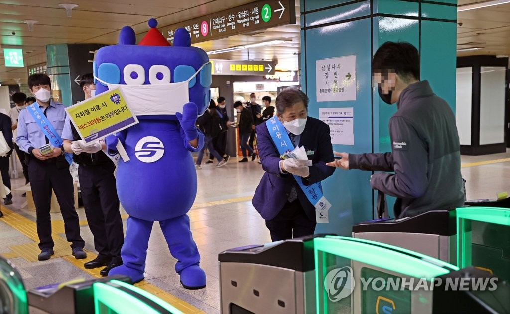 Workers hand out protective masks to commuters at a subway station in southern Seoul on Oct. 13, 2020. (Yonhap)
