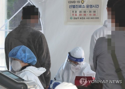 Medical workers carry out new coronavirus tests at a makeshift clinic in southern Seoul on Oct. 20, 2020. (Yonhap)
