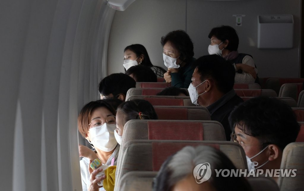 This photo, provided by the Incheon International Airport press pool, shows passengers looking out the windows on an Asiana Airlines flight to nowhere on Oct. 24, 2020. (Yonhap)