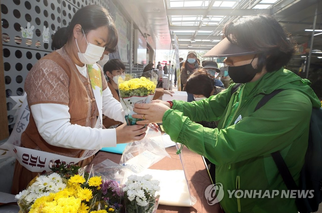 Workers distribute flowers to visitors during a campaign to promote social distancing at a market on the southern resort island of Jeju on Oct. 27, 2020. (Yonhap)