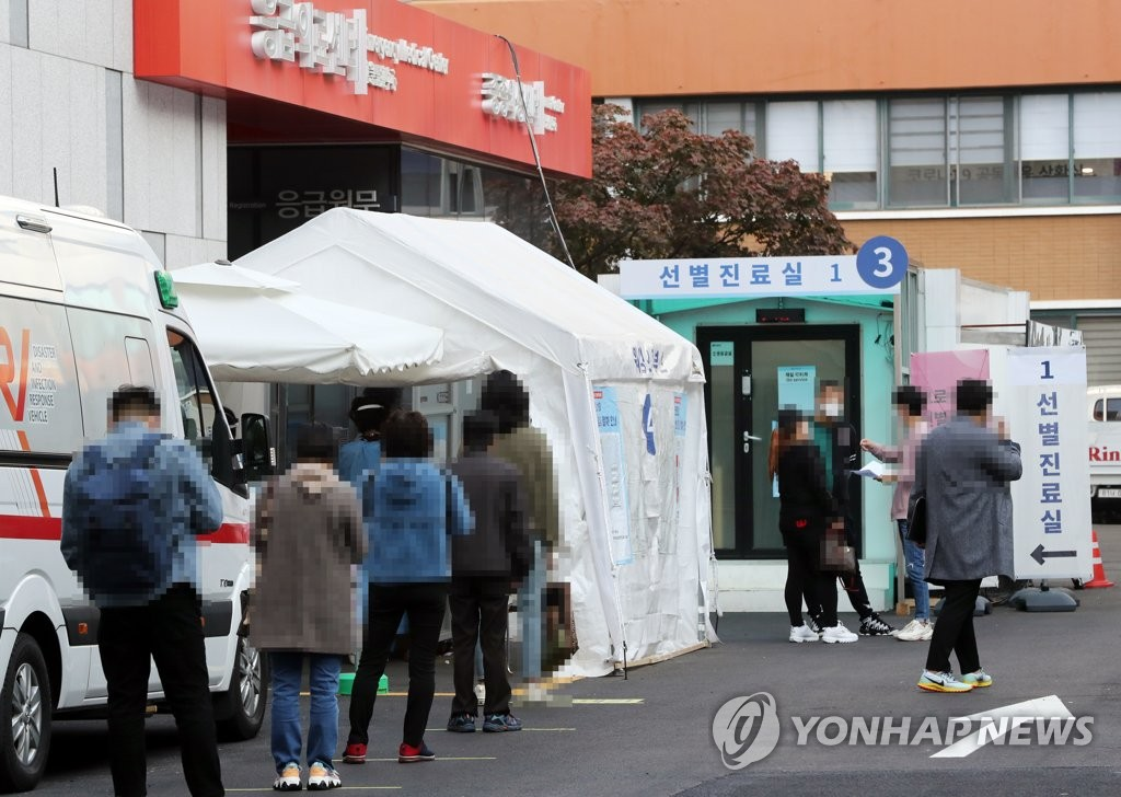 Visitors line up to receive new coronavirus tests at a makeshift clinic in central Seoul on Oct. 28, 2020. (Yonhhap)