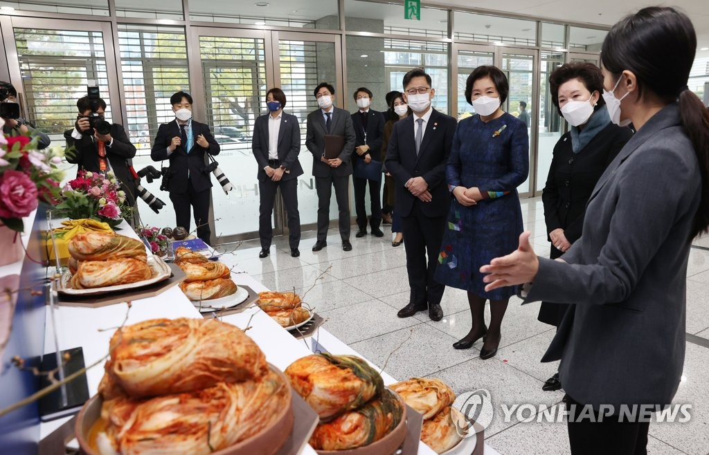 First lady Kim Jung-sook (3rd from R) looks at a display of kimchi at the National Agricultural Cooperative Federation office in Seoul on Nov. 20, 2020. (Yonhap)