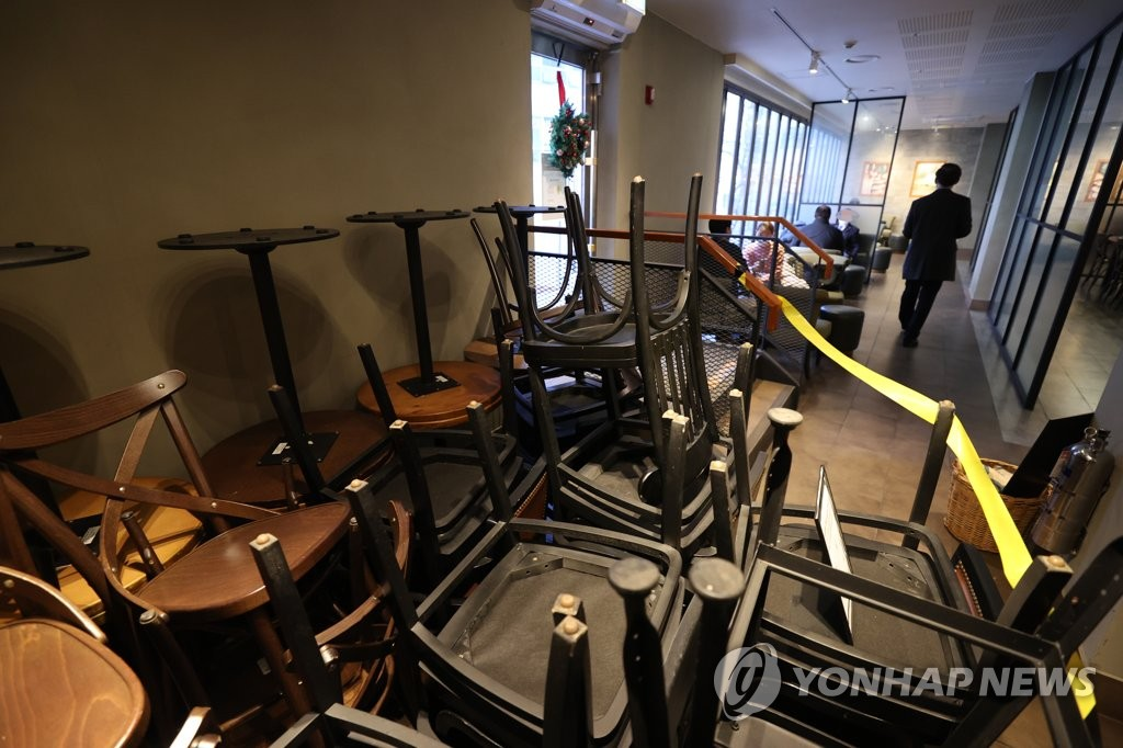 Chairs are placed on tables in a coffee shop in Seoul on Nov. 23, 2020, ahead of Level 2 social distancing, which bans eating inside cafes over fears of COVID-19 outbreaks. (Yonhap)