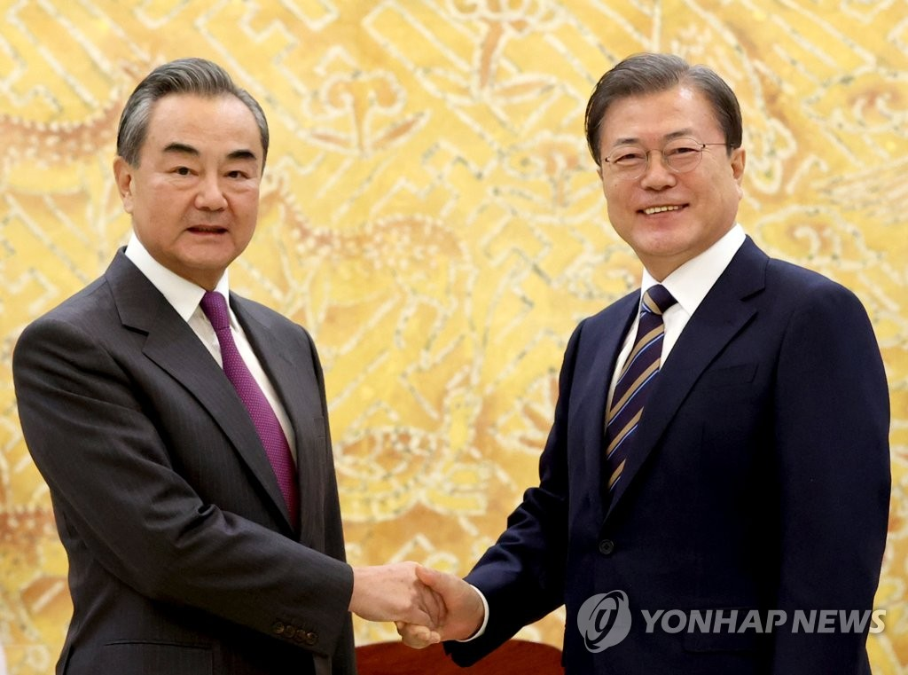 President Moon Jae-in (R) shakes hands with Chinese Foreign Minister Wang Yi during the latter's courtesy call on Moon at the presidential office Cheong Wa Dae in Seoul on Nov. 26, 2020. (Yonhap)