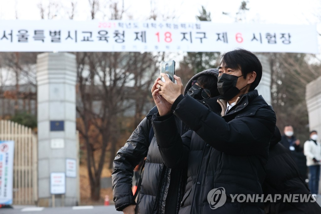 A father takes a selfie with his child at the gate of a high school in Seoul as the student enters the school to take the college entrance exam on Dec. 3, 2020. (Yonhap)