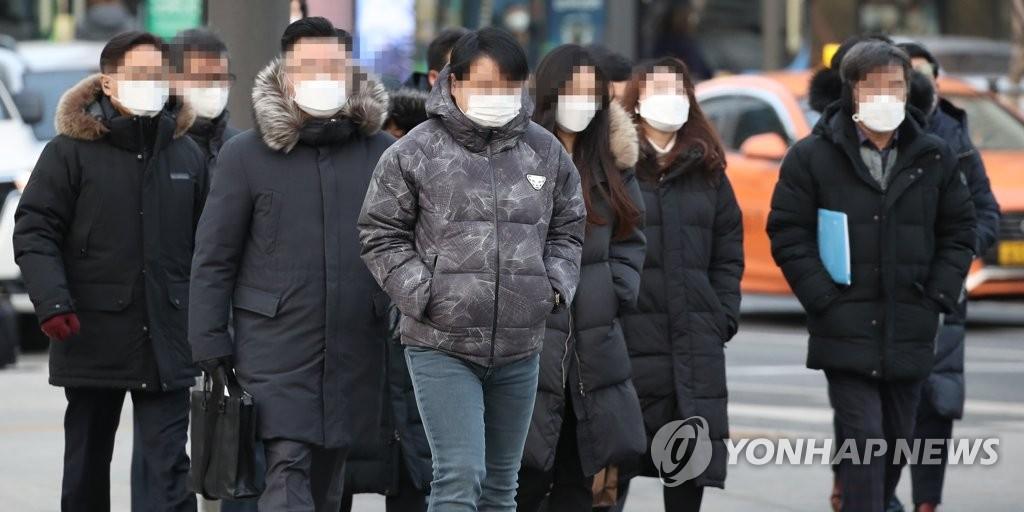 Pedestrians wearing masks cross a road in downtown Seoul on Jan. 4, 2021. (Yonhap)