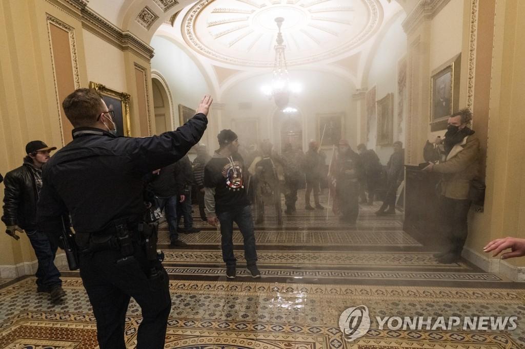연기 자욱한 의사당 안에서 경찰과 대치한 트럼프 지지자들