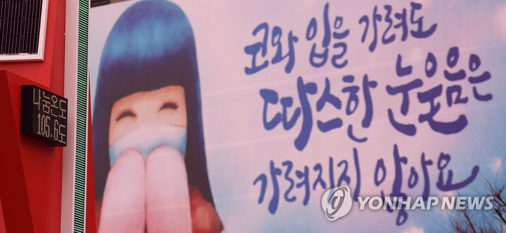 This Jan. 22, 2021, file photo shows a poster created for the Community Chest of Korea's charity campaign of a girl smiling with a protective face mask on amid the new coronavirus pandemic. (Yonhap)