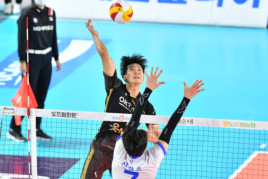 Song Myung-geun of the OK Financial Group OKman (L) hits a spike against the Samsung Fire & Marine Insurance Bluefangs during a men's V-League match at Chungmu Gymnasium in Daejeon, 160 kilometers south of Seoul, on Feb. 2, 2021, in this photo provided by the Korean Volleyball Federation. (PHOTO NOT FOR SALE) (Yonhap)
