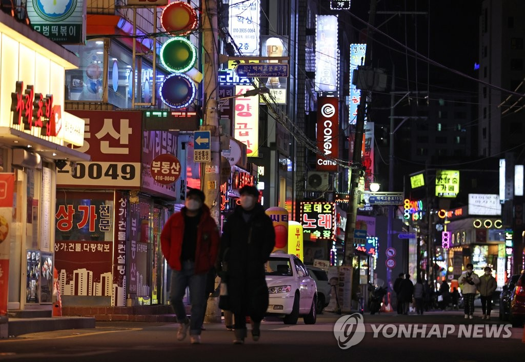 Pedestrians pass a retail strip in southeastern Seoul on Feb. 15, 2021, on the first day of eased social distancing rules for restaurants and cafes. (Yonhap)