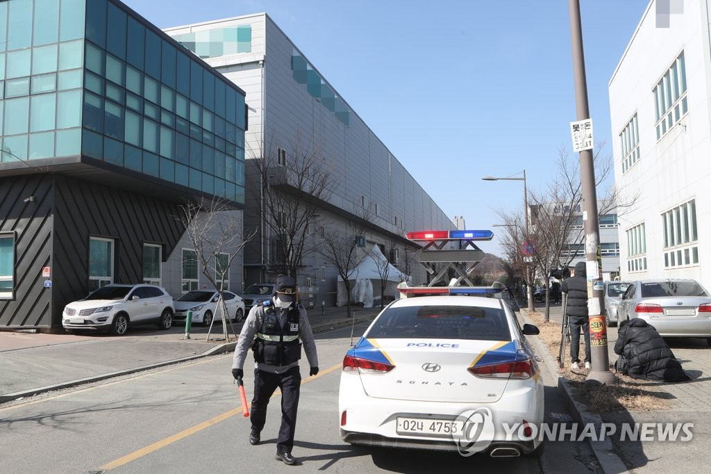 A police officer controls road traffic at an industrial complex in Namyangju, southeast of Seoul, on Feb. 17, 2021, after 114 employees at a factory tested positive for COVID-19. (Yonhap)