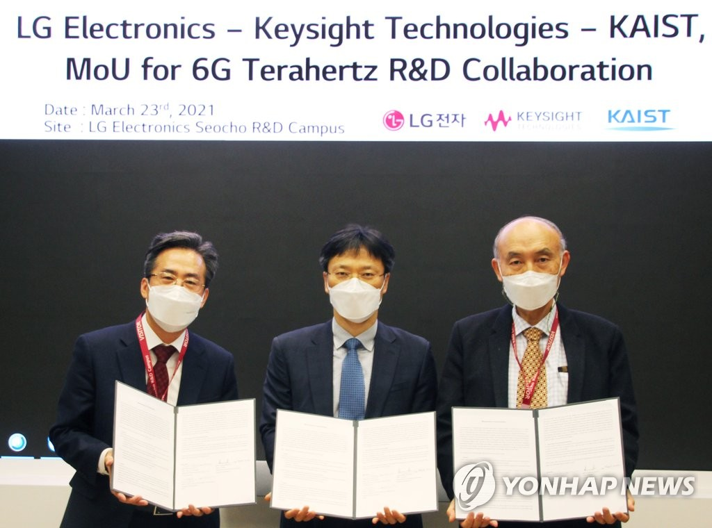 This photo provided by LG Electronics Inc. on March 23, 2021, shows officials from LG Electronics (C), Keysight Technologies (L) and the Korea Advanced Institute of Science and Technology (KAIST) posing for a photo after signing an agreement on cooperation in 6G technology development at LG's R&D center in Seoul. (PHOTO NOT FOR SALE) (Yonhap)