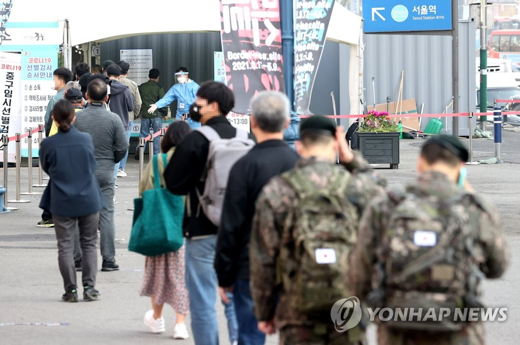 People stand in line to receive coronavirus tests at a makeshift clinic in front of Seoul Station on April 7, 2021. (Yonhap)