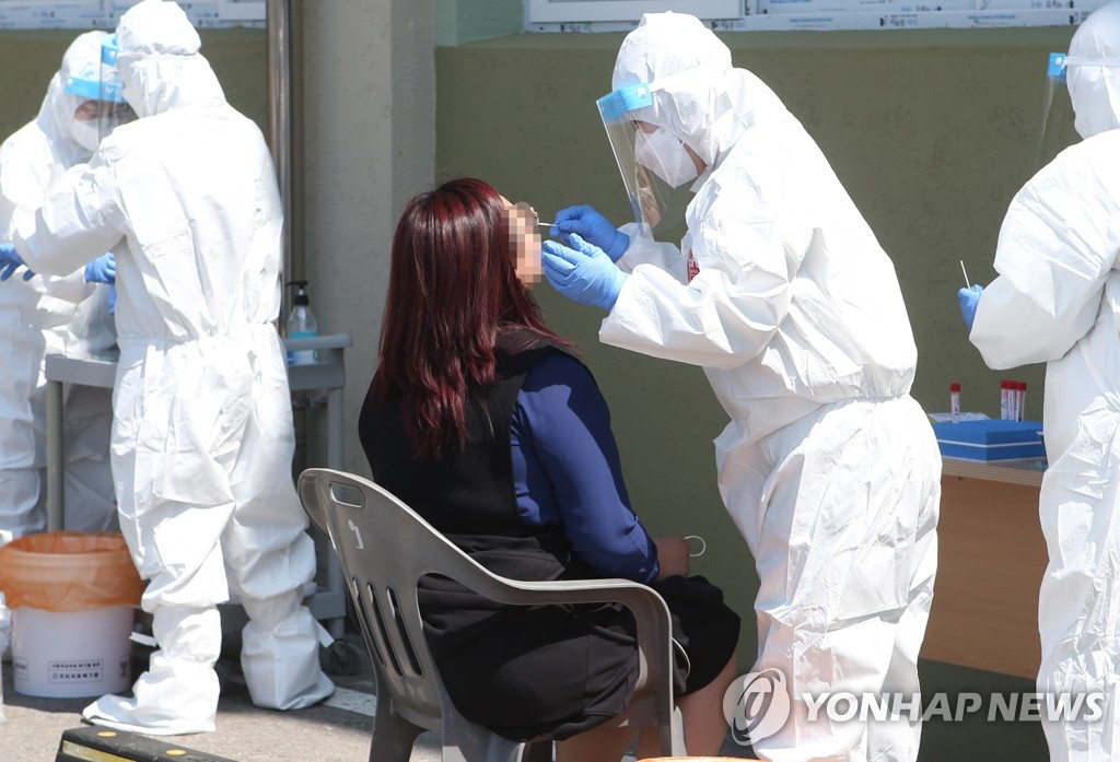 Health care workers test for COVID-19 at a temporary testing station in the county of Okcheon, 174 kilometers south of Seoul, on April 19, 2021. (Yonhap)