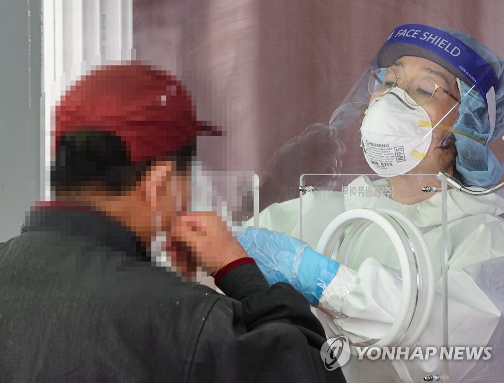 A health care worker conducts a COVID-19 test at a temporary testing center in Seoul Station, central Seoul, on April 20, 2021. (Yonhap)