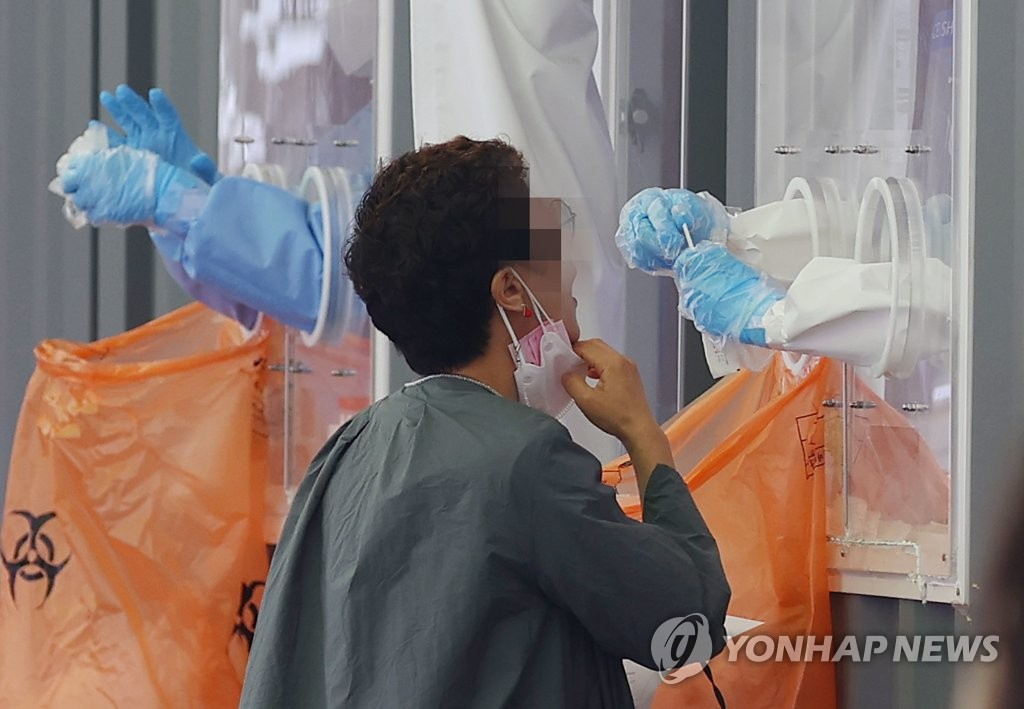 A medical worker takes a sample at a COVID-19 testing station in Seoul on April 22, 2021, with the country reporting 735 new cases on the day, the highest since Jan. 7, when the comparable number was 869. (Yonhap)