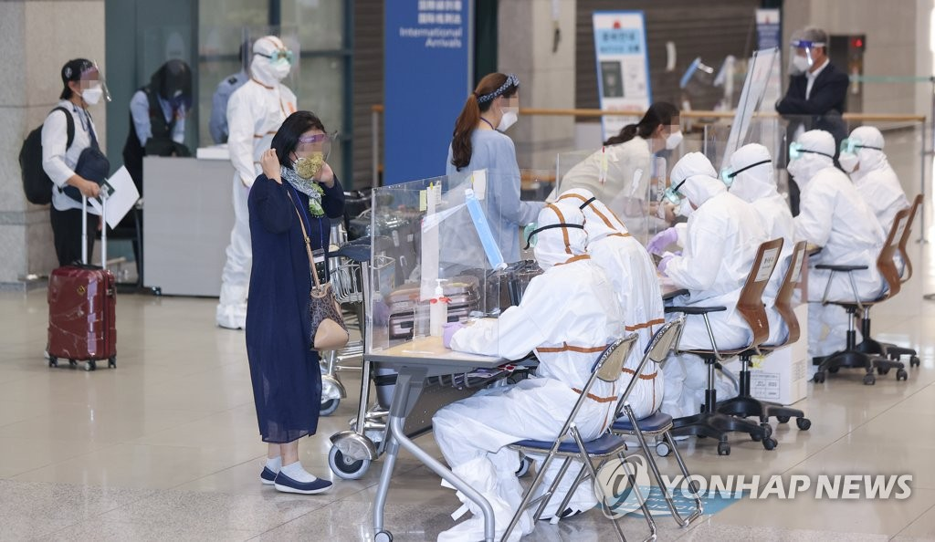 Health workers clad in protective suits guide arrivals from India at Incheon International Airport in Incheon, west of Seoul, on May 4, 2021. (Yonhap)