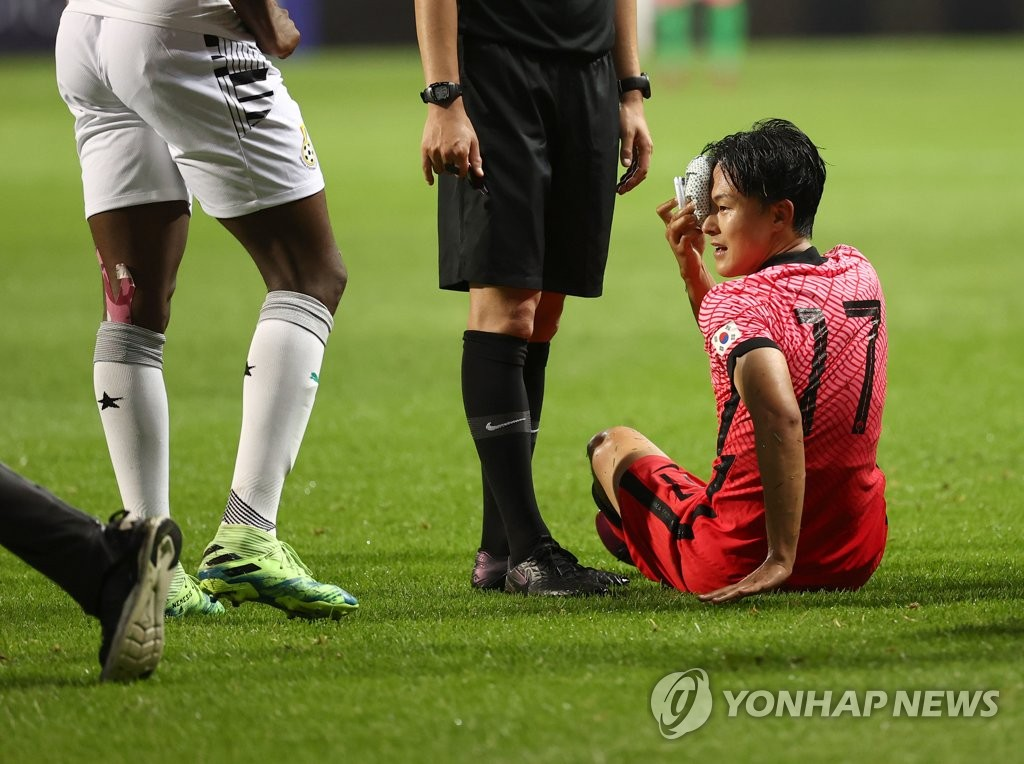 Lee Seung-woo (R) of the South Korean men's Olympic football team stays on the ground after a collision with Jonah Attuquaye of Ghana during a friendly match at Jeju World Cup Stadium in Seogwipo, Jeju Island, on June 15, 2021. (Yonhap)