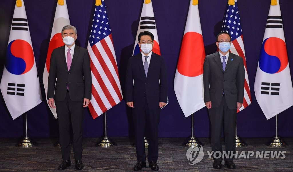 (From L to R) U.S. Special Representative for North Korea Sung Kim stands side by side with his South Korean and Japanese counterparts -- Noh Kyu-duk and Takehiro Funakoshi -- at the start of their trilateral talks on efforts to denuclearize Pyongyang at the Lotte Hotel in central Seoul in this pool photo on June 21, 2021. (Yonhap)