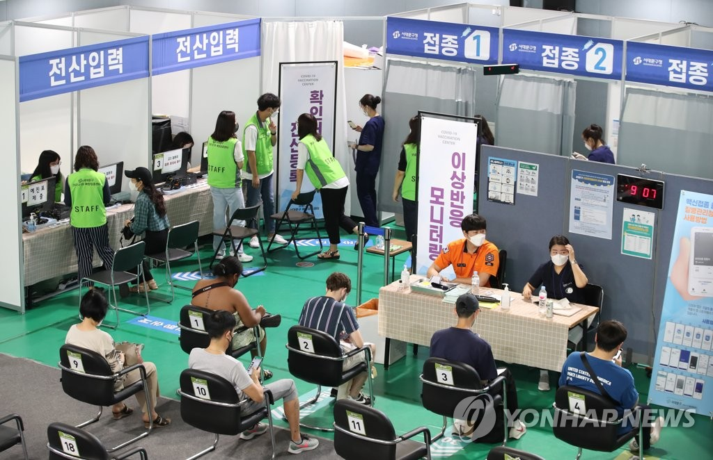 People wait in line to get COVID-19 vaccine shots in a vaccination center in western Seoul on Aug. 11, 2021. (Yonhap)