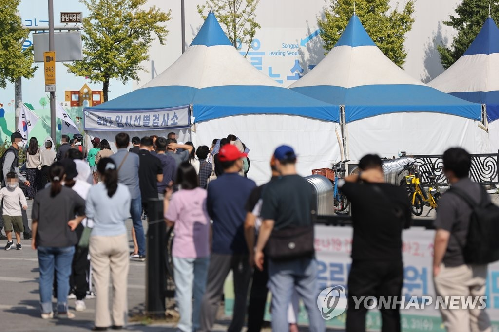 People wait in line to get tested for COVID-19 at a temporary screening center in southern Seoul on Oct. 1, 2021. (Yonhap)